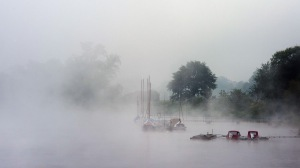Morning fog covers the view to sail boat